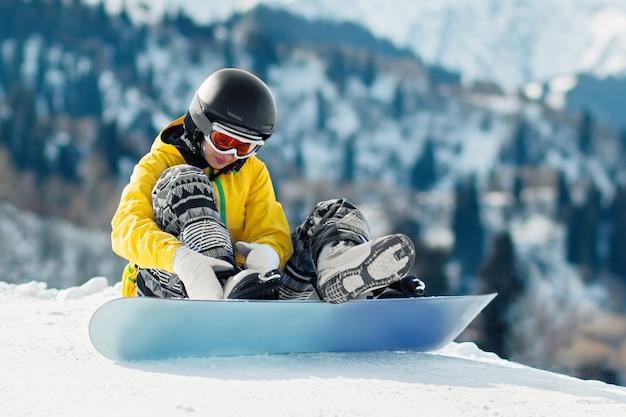 Le snowboarder de la jeune femme s'assied dans la neige et attache des attaches sur un snowboard avant la descente