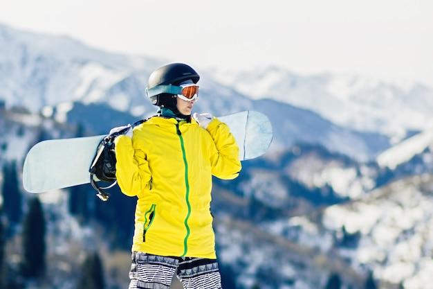 Snowboarder de jeune femme avec snowboard sur ses épaules regarde la piste de ski, espace de copie