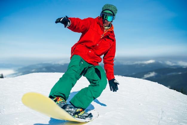 Snowboarder à lunettes pose avec planche en mains