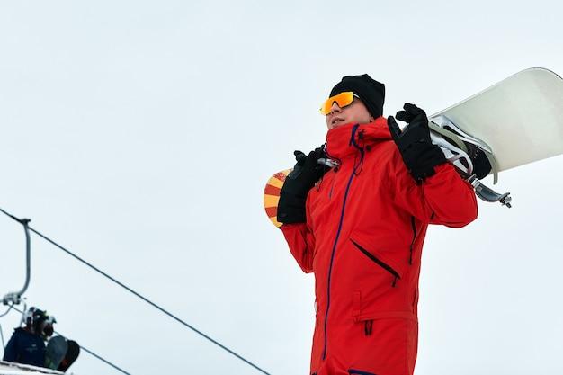 Snowboarder mâle dans un costume rouge marchant sur la colline enneigée avec snowboard, ski et snowboard concept
