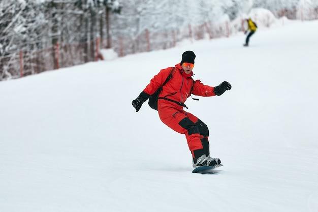 Snowboarder mâle dans un costume rouge monte sur la colline enneigée avec snowboard, ski et snowboard concept