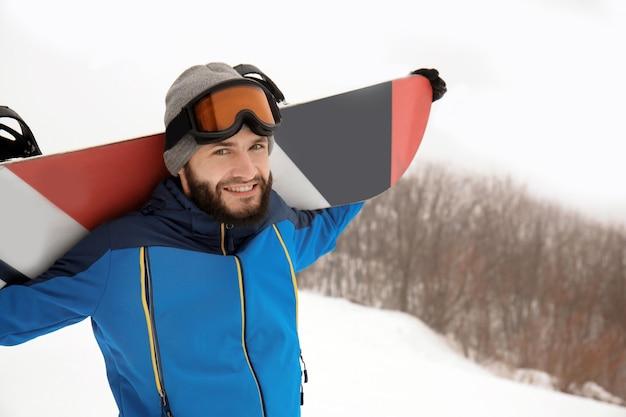 Snowboarder mâle sur la pente à la station d'hiver