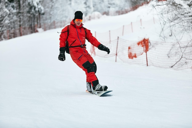 Un snowboarder masculin en costume rouge monte sur la colline enneigée avec un concept de snowboard, de ski et de snowboard.