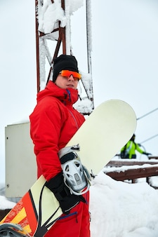 Snowboarder masculin dans un costume rouge marchant sur la colline enneigée avec concept de snowboard, de ski et de snowboard.