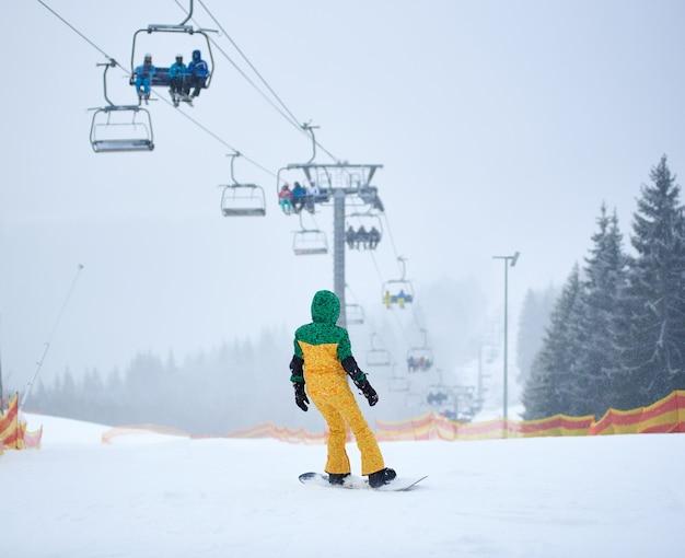 Snowboarder méconnaissable glissant sur pente avec filet. télésiège transportant des gens. paysage d'hiver brumeux. vue arrière