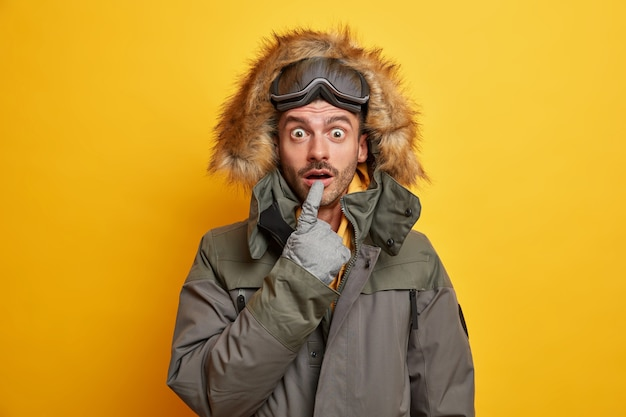 Le snowboardeur surpris émotionnel garde la bouche ouverte des repos de merveille dans les montagnes aime les sports d'hiver porte une veste chaude avec capuche en fourrure va skier.