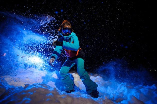 Snowboardeuse active vêtue d'un vêtement de sport orange et bleu sur la piste enneigée