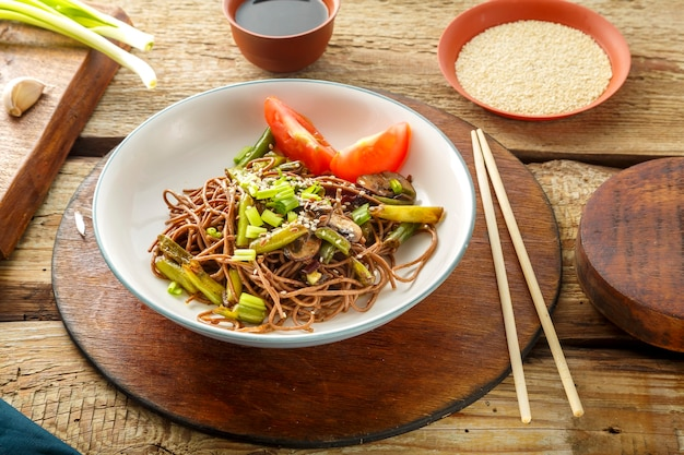 Soba aux champignons, haricots verts et graines de sésame dans une assiette sur un support sur une table en bois à côté de baguettes et sauce soja et ail. photo horizontale