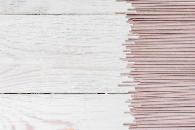 Soba cru sur une table en bois blanc. cuisine japonaise traditionnelle. vue de dessus, espace de copie