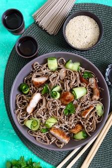 Soba froid au poulet, concombres frais, sauce et sésame. salade froide classique aux nouilles de sarrasin. nourriture japonaise. cuisine asiatique traditionnelle. vue de dessus, pose à plat.