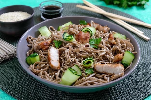 Soba froid au poulet, concombres frais, sauce et sésame. salade froide classique aux nouilles de sarrasin. nourriture japonaise. cuisine asiatique traditionnelle