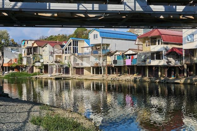 Sochy, russie - 14 septembre 2020 : la rive de la rivière dagomys est entièrement aménagée avec de petits chalets avec garages pour bateaux
