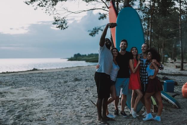 Société des adolescents faisant selfie sur la plage.