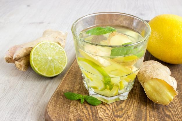 Soda au gingembre avec citron, menthe, gingembre et glace sur bois rustique