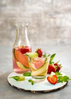 Soda aux fraises et au concombre sur fond gris