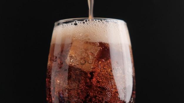 Soda avec de la glace sur un gros plan fond noir