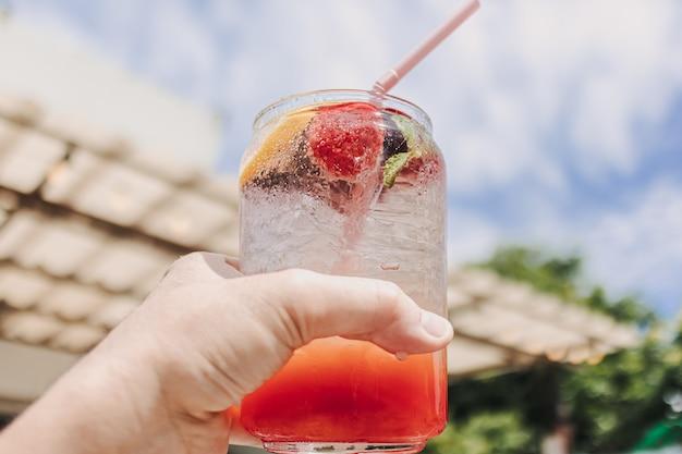 Soda italien rose de fruits mélangés contre le ciel ensoleillé d'été