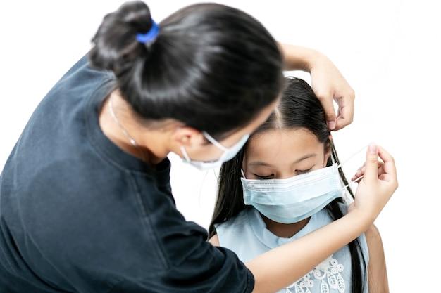 Sœur aidant sa petite sœur portant un masque chirurgical. concept de protection contre les virus.
