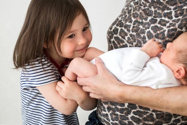 Sœur aînée embrasse sa soeur nouveau-née. grand-mère tient sa petite-fille nouveau-née dans ses bras
