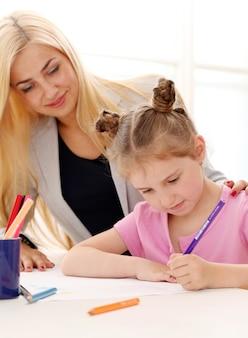 La sœur aînée enseigne à la sœur cadette comment dessiner