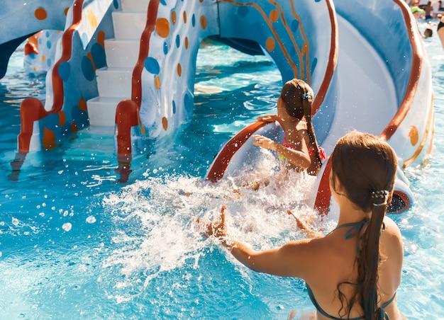 La sœur aînée prudente attrape son mignon petit qui glisse le long du toboggan jusque dans la piscine et éclabousse