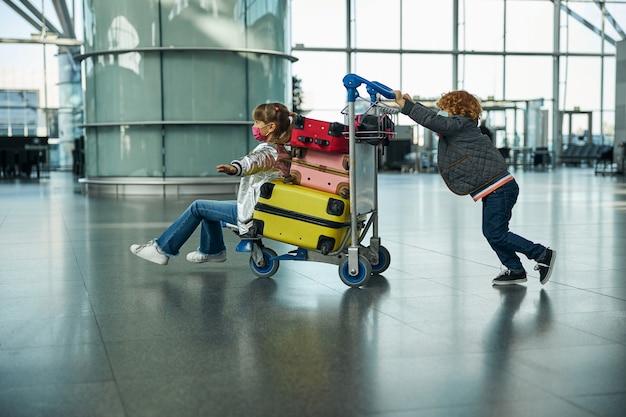 Sœur chevauchant une charrette pendant que son frère pousse derrière