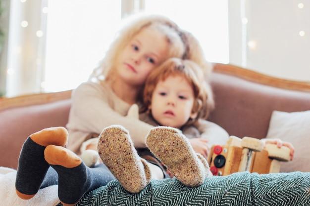 Sœur embrasse petit frère sur le canapé, se concentre sur les jambes
