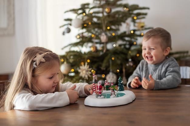 Sœur et frère jouent avec des figurines en céramique pour noël
