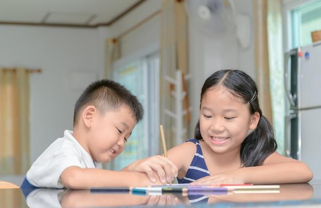 Soeur et frère peignent couleur sur papier au crayon.