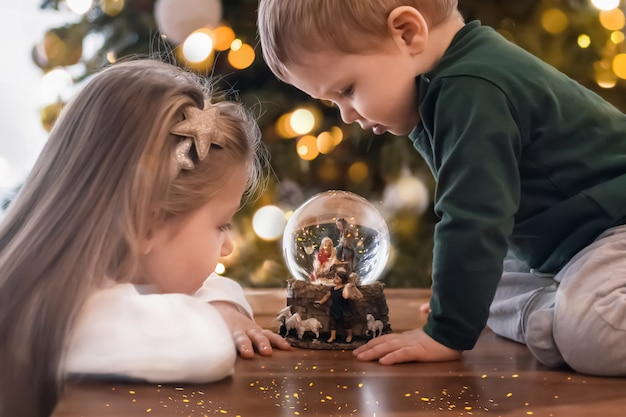 Sœur et frère regardant une boule de verre avec une scène de la nativité de jésus-christ dans une boule de verre sur un arbre de noël