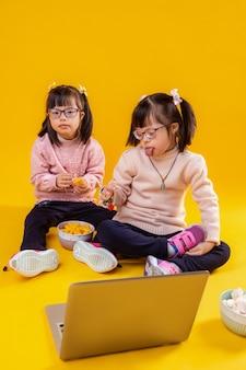 Avec sœur jumelle. insolite petite enfant mignonne montrant sa langue tout en regardant les dessins animés avec sa soeur