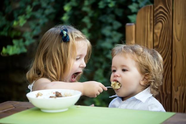 Sœur nourrissant un bébé garçon fille nourrit son frère avec une cuillère de nourriture pour enfants