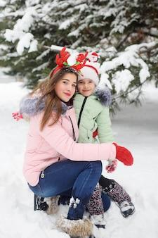 La sœur plus jeune et plus âgée s'amuse sur le fond de la neige et de la forêt. plaisir de noël