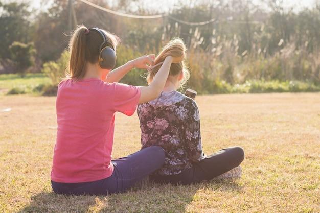 Sœur portant un casque attachant ses cheveux de soeurs dans le parc