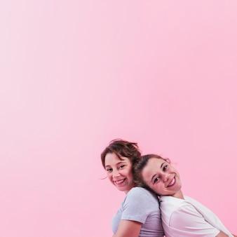 Sœur souriante assise dos à dos se moquer sur fond rose