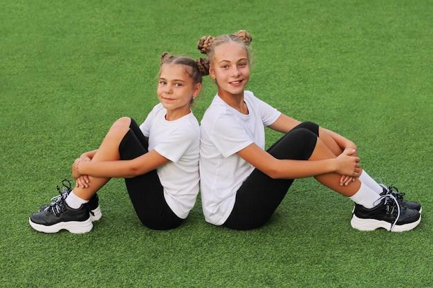 Des sœurs adolescentes en tenue de sport sont vues assises dos à dos sur l'herbe verte du stade et regardant directement la caméra. t-shirts blancs.