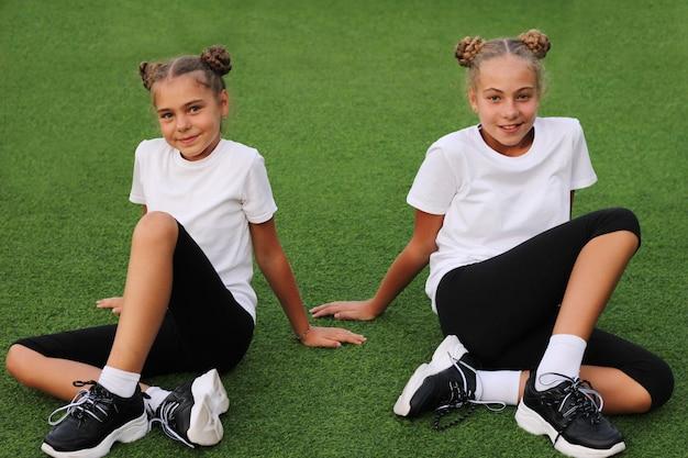 Des sœurs adolescentes en tenue de sport sont vues assises sur l'herbe verte du stade et regardent directement la caméra. t-shirts blancs. le sport dans nos vies.