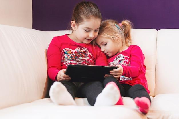 Sœurs à l'aide de tablette sur le canapé