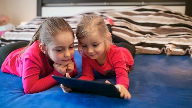 Sœurs à l'aide de la tablette sur le lit