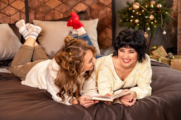 Sœurs allongées sur le lit et lisant un livre. ils rient et célèbrent le nouvel an et noël. il y a des cadeaux et des branches de sapin décorées avec des boules dorées.
