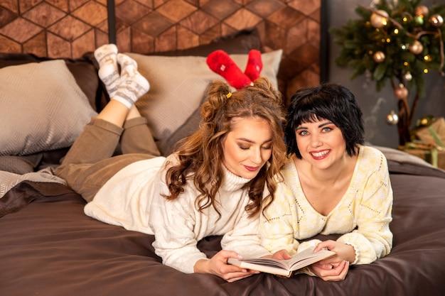 Sœurs allongées sur le lit et lisant un livre. ils sourient et célèbrent le nouvel an et noël. il y a des cadeaux et des branches de sapin décorées avec des boules dorées.