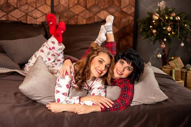 Sœurs allongées sur le lit en pyjama. ils sourient et célèbrent le nouvel an et noël. il y a des cadeaux et des branches de sapin décorées avec des boules dorées.