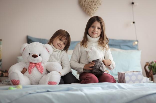 Soeurs avec des cadeaux tricotés dans un véritable intérieur