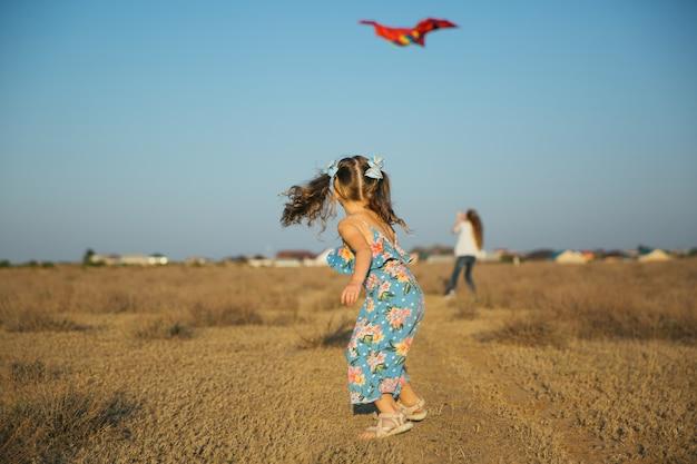 Sœurs courir et jouer avec le cerf-volant sur le terrain