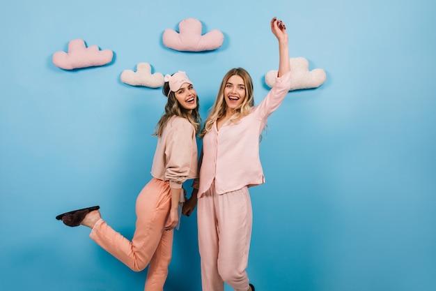 Sœurs excitées en vêtements de nuit dansant sur un mur bleu avec des nuages de jouets