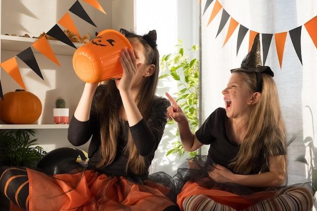 Des sœurs folles de dix et sept ans en costumes de sorcière à halloween célèbrent la fête ...