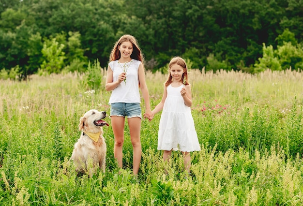 Sœurs heureux avec chien mignon sur prairie d'été en fleurs