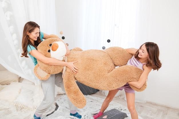 Sœurs jouant et s'amusant avec un ours en peluche bug