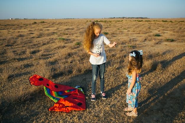 Les soeurs jouent avec le cerf-volant sur le terrain