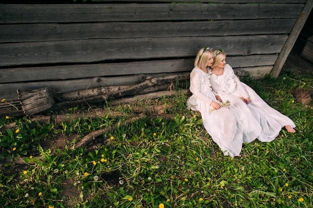 Soeurs jumelles assis à un mur en bois